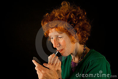 Ginger woman colouring her lips