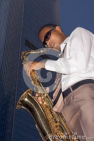 Giocatore di sassofono urbano sulla priorità bassa del grattacielo