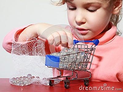 Gioco sveglio di cura della ragazza con il carrello di acquisto del giocattolo