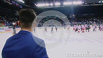 Giornalista con microfono alla partita di hockey su una grande arena sul ghiaccio video d archivio