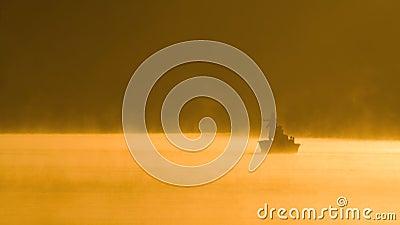 Giorno di pesca nebbioso su un lago