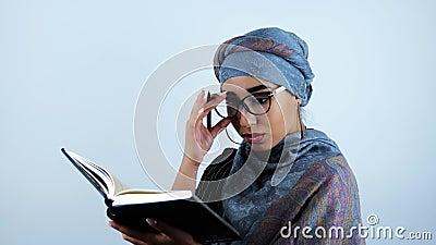 Giovane bella donna araba di affari sorpresa toccando gli occhiali dopo l'individuazione delle informazioni necessarie in taccuin archivi video