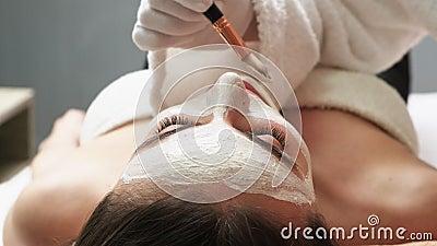 Giovane bellezza visita il salone termale e prende una maschera per la cura della pelle del volto video d archivio
