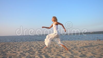 giovane bello funzionamento felice della donna e saltare sulla spiaggia archivi video