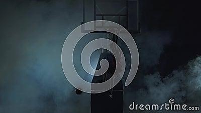 Giovane in buona salute che gioca pallacanestro nel fondo nero con le nuvole di fumo La camicia rossa e nero d'uso mette stock footage