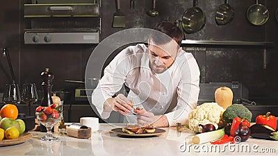 Giovane chef decora il suo piatto speciale con alcuni verdi Lui lavora in una cucina moderna archivi video