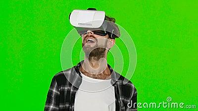 Giovane con la cuffia avricolare di realtà virtuale di VR sulla sua testa Schermo verde Fine in su stock footage