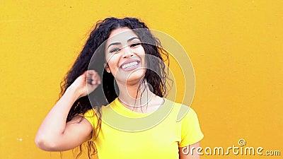 Giovane donna araba Casual sulla parete gialla per strada che sorride e ride stock footage