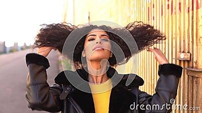 Giovane donna araba che cammina all'aperto muovendo i capelli ricci neri archivi video