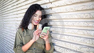 Giovane donna araba con cuffie che usa il suo smartphone all'aperto stock footage