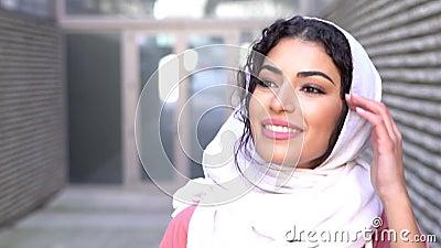 Giovane donna araba indossa il velo hijab mentre cammina nel centro della città archivi video