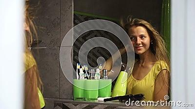 Giovane donna asciuga capelli con asciugacapelli e sorrisi, riflesso nello specchio stock footage