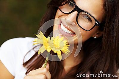 Giovane donna bella in vetri che tengono un fiore