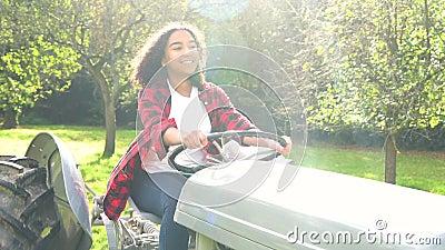 Giovane donna biraziale dell'adolescente che guida un trattore grigio attraverso un meleto soleggiato stock footage