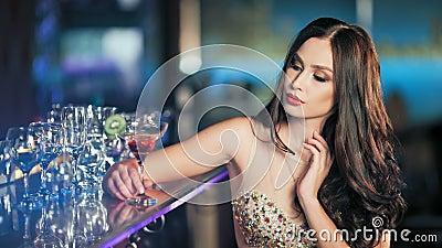 Giovane donna castana di bellezza che si siede alla barra con bicchiere di vino nell'interno di lusso stock footage