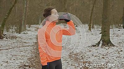 Giovane donna che beve acqua nel parco Attraente isotonica tenera che beve una bottiglia dopo un allenamento duro Bambina che rif stock footage