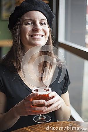 Giovane donna che beve la birra chiara di Inda