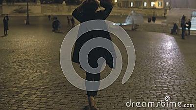 Giovane donna che cammina nella città di sera da solo Femmina attraente che aspetta qualcuno nel centro urbano, al quadrato stock footage