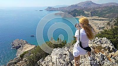 Giovane donna che prende le immagini di paesaggio Mediterraneo video d archivio