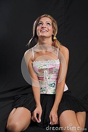 Giovane donna che si siede e che osserva in su