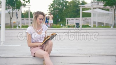 Giovane donna che si siede sulle scale che leggono un libro nel parco urbano video d archivio