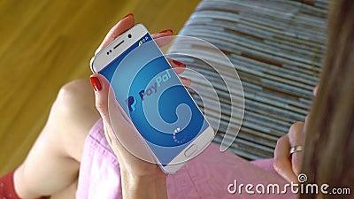 Giovane donna che tiene un telefono cellulare con il carico del cellulare app di Paypal Clip concettuale dell'editoriale 4K video d archivio