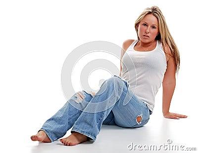 Giovane donna con i jeans strappati che si siedono