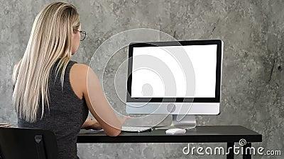 giovane donna di affari che lavora nell'interno dell'ufficio sul pc sullo scrittorio, scrivere, esaminante schermo Visualizzazion video d archivio