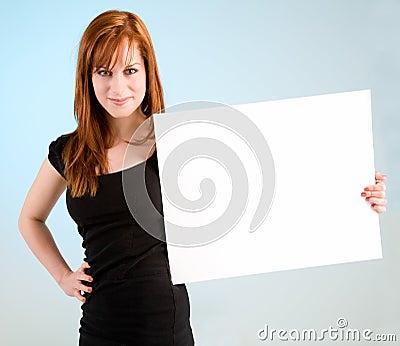 Giovane donna di Redhead che tiene un segno bianco in bianco