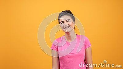 Giovane donna in maglietta rosa che sorride duro e che ride con le emozioni naturali stock footage