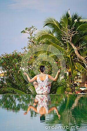 Giovane donna nella posa del loto nel paesaggio tropicale