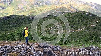 Giovane donna viaggiatrice in piedi su una montagna e usa il suo smartphone video d archivio