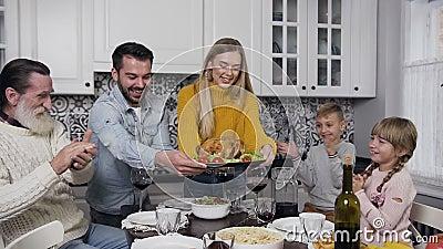 Giovane e donna allegra che indossano il tacchino arrosto da tavola durante la festa del Ringraziamento stock footage