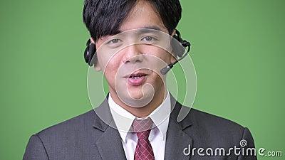Giovane funzionamento asiatico bello dell'uomo d'affari come rappresentante della call center video d archivio