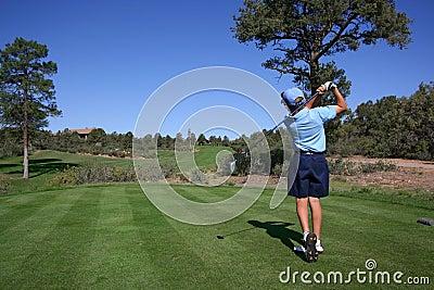 Giocatore di golf giovane che colpisce fuori dal T