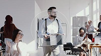 Giovane impiegato maschio caucasico felice che lascia lavoro moderno dell'ufficio con una scatola, un applauso del gruppo e ringr archivi video