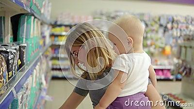 Giovane madre attraente in vetri che tengono il suo bambino lei armi mentre scegliendo i pannolini sugli scaffali in video d archivio