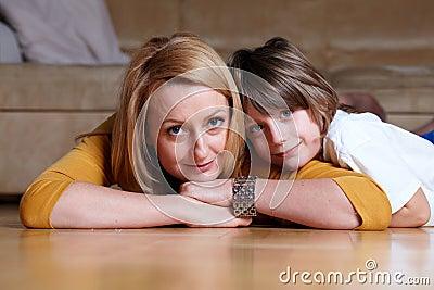 Giovane mamma felice che si trova sul pavimento con il suo figlio