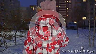 Giovane ragazza con cappello invernale e giacca in giù che cammina per strada in inverno con vista posteriore serale Ragazza adol archivi video