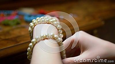 Giovane ragazza si toglie le perline bianche con le mani chiusura video d archivio