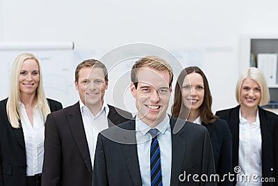 Giovane responsabile di Handsom con un gruppo felice dietro lui