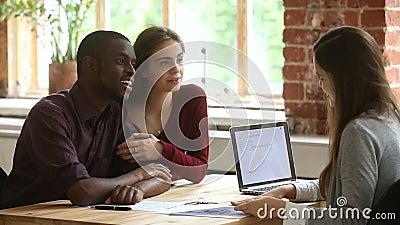 Giovane riunione multi-etnica di ipoteca di pianificazione delle coppie con l'agente immobiliare archivi video