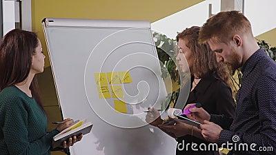 Giovane team americano che lavora con una strategia di marketing vicino al White Board in azienda archivi video
