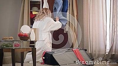 Giovane turista caucasica mette roba in valigia e sacchetto di chiusura Donna stanca e allegra che prepara un viaggio a archivi video