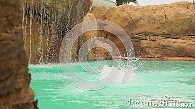 Giovane uomo attraente si tuffa in piscina nel parco acquatico archivi video