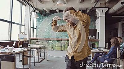 Giovane uomo d'affari bello che fa ballo di vittoria circa il riuscito risultato Maschio felice all'ufficio d'avanguardia moderno stock footage