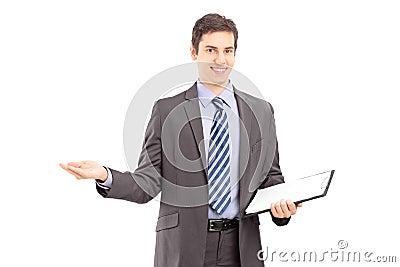 Giovane uomo professionale che tiene una lavagna per appunti e che gesturing con l ha