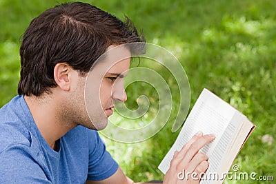 Giovane uomo serio che legge un libro