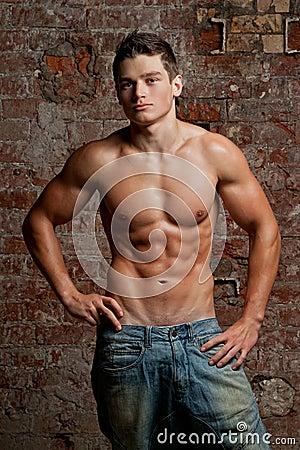 Giovane uomo sexy nudo muscolare che propone in blue jeans