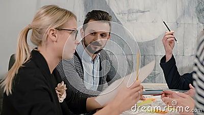Giovani architetti del gruppo creativo di piccola impresa che si incontrano nell'ufficio startup attivamente che discute le nuove archivi video